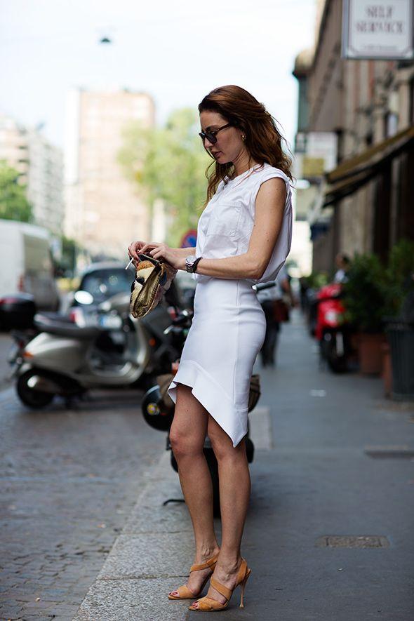 white sleeveless shirt, asymmetrical skirt and tan sandal heels............