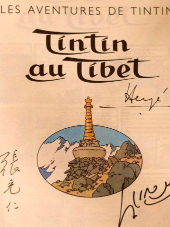 Front page of the comic The adventures of Tintin - Tintin au Tibet signed by the author Herge (R) and the Dalai Lama (R bottom).