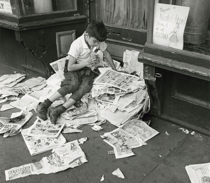 André Kertész ; New York (boy eating ice cream on a pile of newspapers) October 12, 1944.