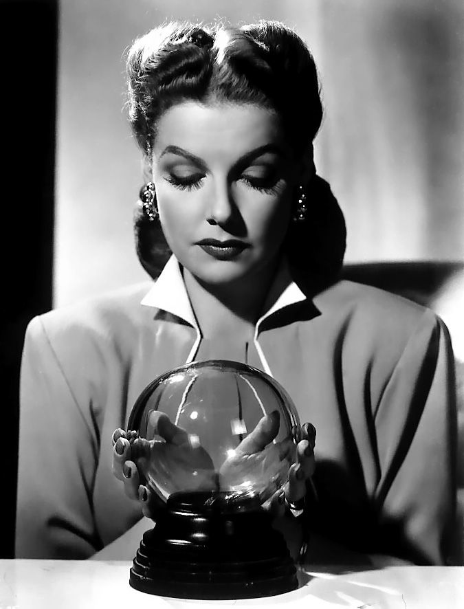 Stellar Vintage #359: Ann Sheridan reads the future in style with stud hoop earrings, spider leg eyelashes, popped collar and keyhole neckline.