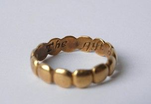 Gold posy ring with inscription. The hoop forms a series of ovals.