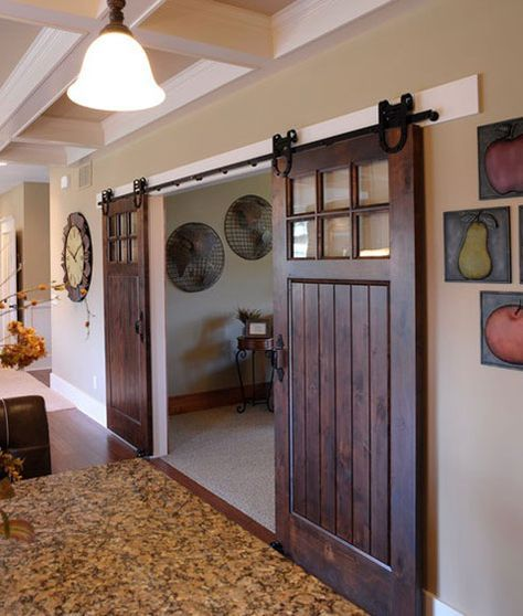 Sliding Barn Doors: Your home doesn't have to be country to have sliding barn doors. These doors look fabulous in this contemporary style home. The dark hardware accents the warm wood finish.