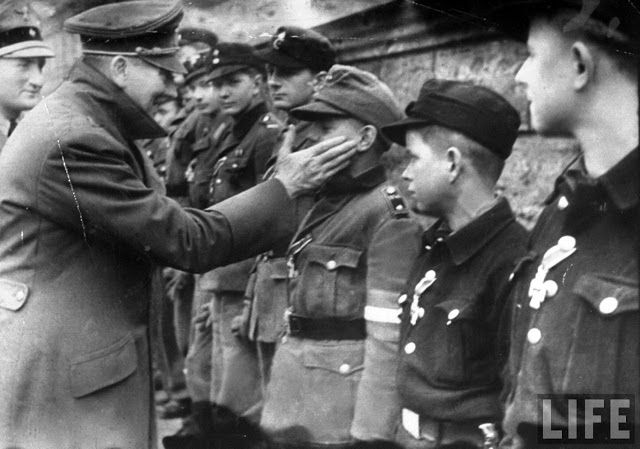 Adolf Hitler greeting boy soldiers of the Hitler Youth in Berlin, March 20, 1945. http://simon-rose.com/books/the-doomsday-mask/historical-background/
