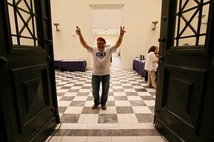 """A 'No' supporter flashes V signs from inside the Zappeion conference center in Athens, Greece July 5, 2015. Greeks voted overwhelmingly """"No"""" on Sunday in a historic bailout referendum, partial results showed, defying warnings from across Europe that rejecting new austerity terms for fresh financial aid would set their country on a path out of the euro. REUTERS/Jean-Paul Pelissier TPX IMAGES OF THE DAY"""