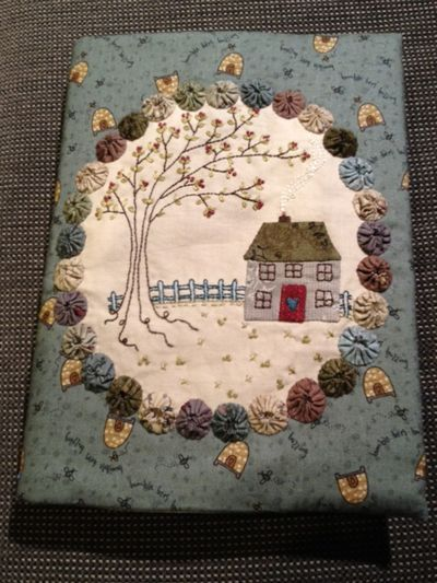 A pretty journal cover by Lynette Anderson. Love the yoyo frame and house and tree