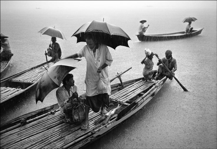 Bangladesh. Sylhet. Khaliajuri village. In the monsoon rain a man returns to his home from the bazaar with the shopping. The annual flooding separates the village into small islands so movement between them is done by small wooden ferry boats.