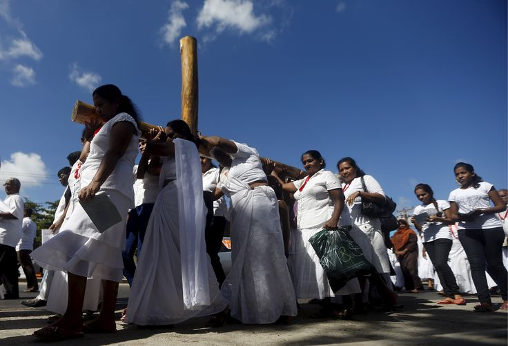 Colombo, Sri Lanka Catholic devotees carry a wooden cross during a Good Friday mass at a church.
