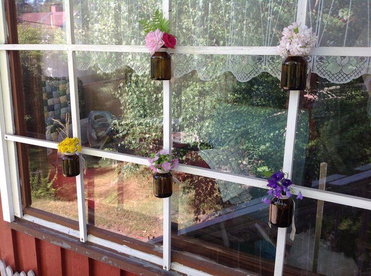 kuistin ikkunoiden ristikoihin ripustin vanhoja lasipurkkeja kukkia varten