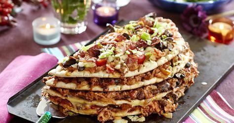 Varm smörgåstårta med extra allt. Fyll den med kryddig färsröra och bacon och toppa med ost. Gratinera och njut!