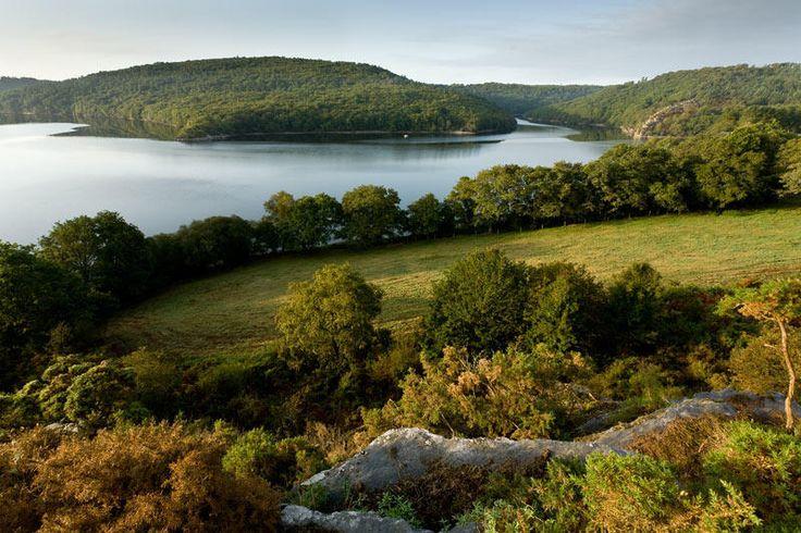 """Lac de Guerlédan - """"Entre Mûr-de-Bretagne et l'Abbaye de Bon Repos, le lac de Guerlédan déroule ses rives boisées au cœur de l'Argoat. Ce magnifique plan d'eau, formé par la construction d'un barrage hydroélectrique, se niche dans le vaste massif forestier de Quénécan. Un paradis pour les amateurs de tourisme vert !"""""""