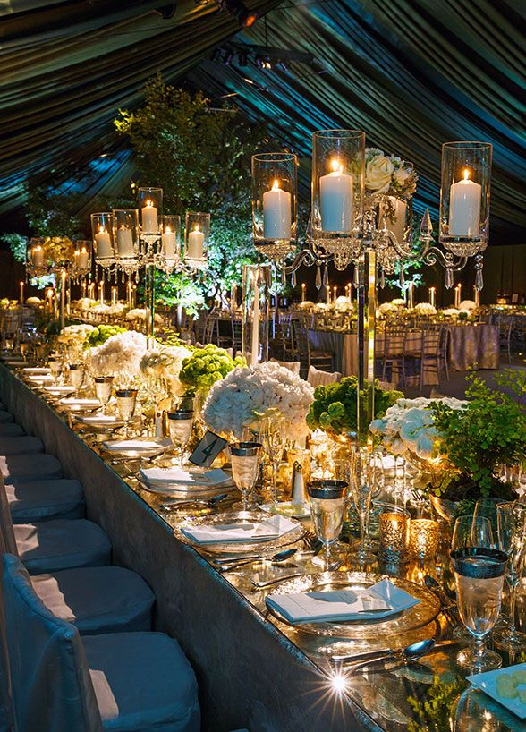Gorgeous crystal candelabras holding pillar candles compliment the textured gold votives that surround below. #WeddingCenterpieces