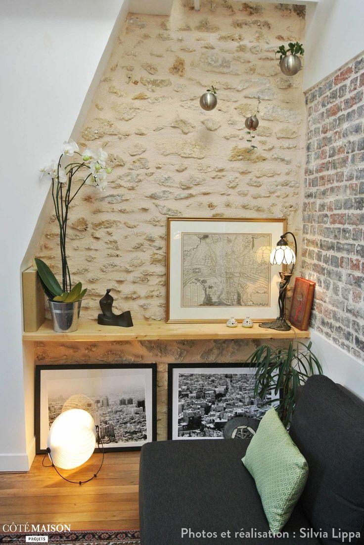 Salon cosy dans espace atypique avec mur en briques et pierres apparentes.