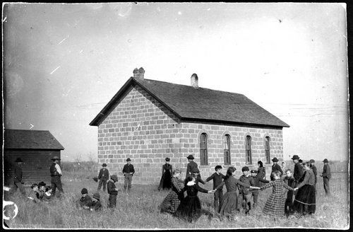 Centennial School, Montgomery County, Kansas This photograph shows children playing at Centennial School, District #9, Montgomery County, Kansas. The school house is made of stone. Date: 1892