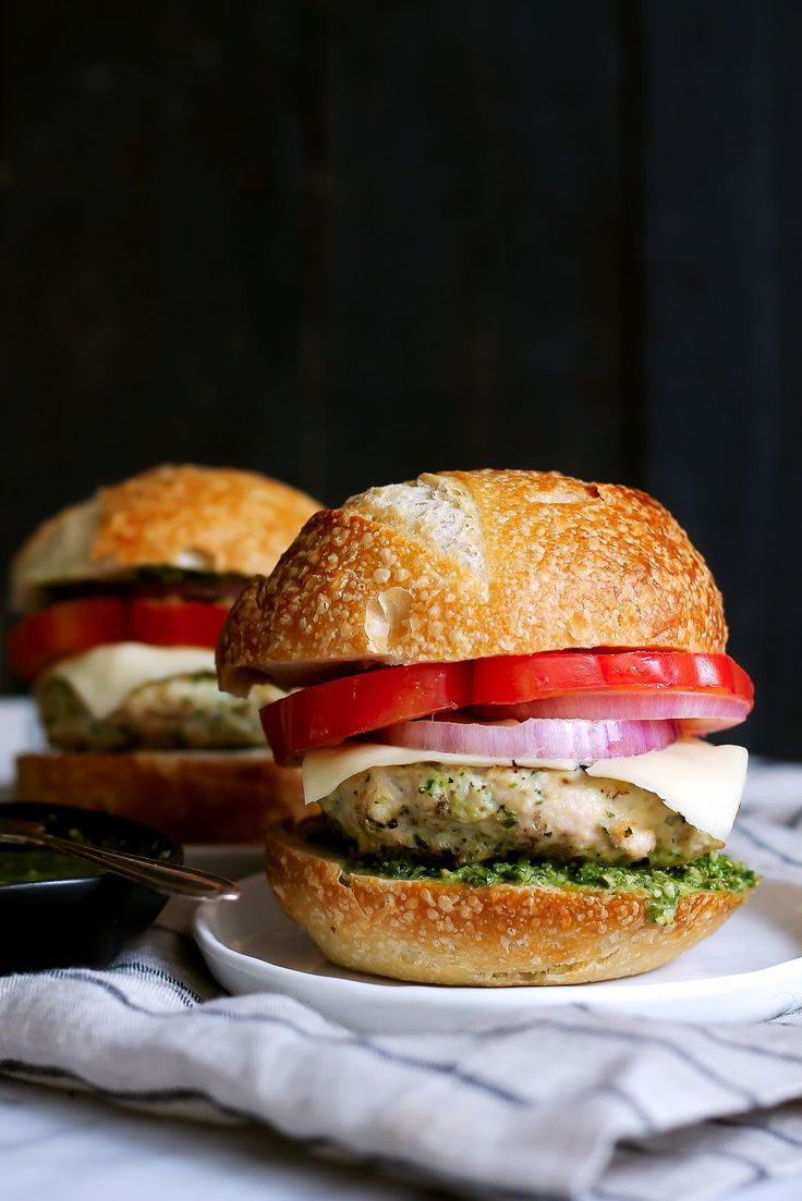 BEST CHICKEN BURGERS EVER -- topped with an easy homemade pesto, mozzarella and all the toppings you like. Grill or bake them!