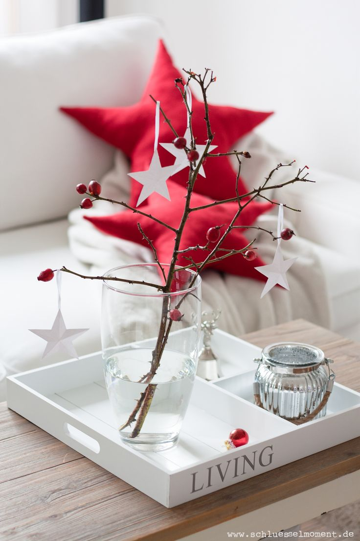 White tray, rose hip, paper stars and star pillows for Christmas