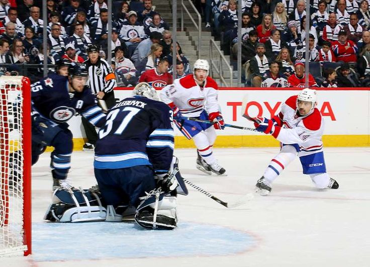 Coming in fast:   Tomas Plekanec of the Montreal Canadiens shoots the puck past goaltender Connor Hellebuyck of the Winnipeg Jets for a first period goal on Jan. 11 in Winnipeg, Canada. Montreal won 7‐4.