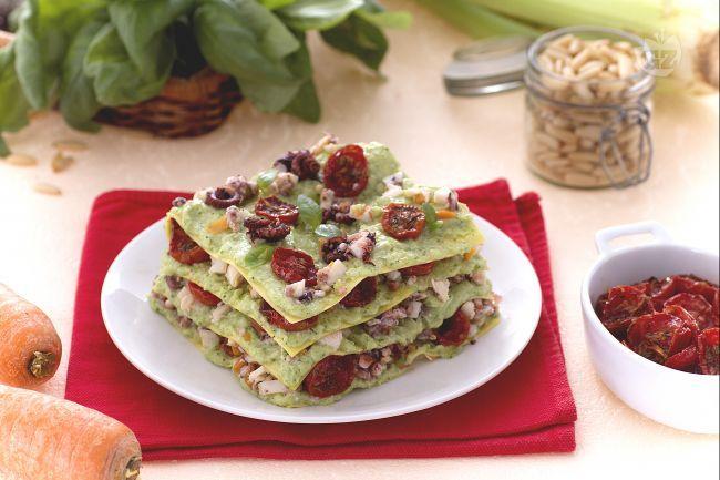 Le lasagne con ragù di polpo sono un primo piatto delicato con polpo, pesto di zucchine e pomodorini confit tra strati di sottile pasta all'uovo.