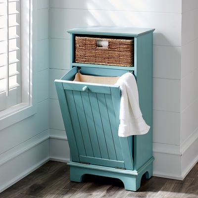 Our handsome wood cabinet features one hand-woven banana leaf basket and a lower wainscot-detailed door with tilt-out laundry hamper.