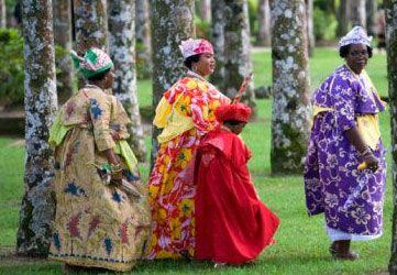Kotomisi en angisa uit Suriname    De kotomisi (gelaagde jurk) is tijdens de slavernij ontstaan. Vrouwelijke rondingen van de Creoolse jongedames verdwijnen in deze verhullende kleding geheel. Plantage-eigenaren met begerige blikken kwamen door deze onaantrekkelijk makende 'camouflagekleding' (kuisheidversterkende kleding) minder gauw in de verleiding deze vrouwen te benaderen. 'Koto' betekent rok en 'misi' betekent juffrouw.