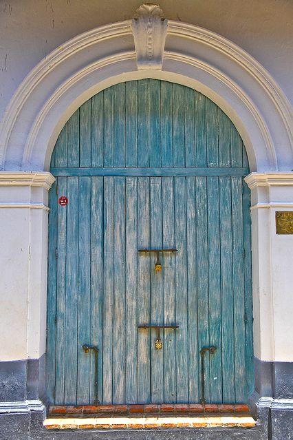 Blue wooden door in Calle Estanco del Tabaco outside La Passion Hotel - Cartagena de Indias, Colombia. By Cedric Converset