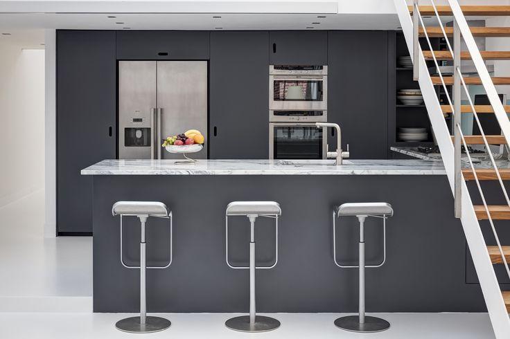Carrara marble worktop island. Custom built kitchen in dark grey.