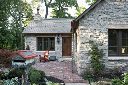The Gatehouse  http://www.murphycodesign.com  Front facade with Platteville limestone walls reclaimed from the 1889 Lake St. bridge pilings in Minneapolis. The Chimney pot was an antique the owner had found years ago.    Photos by Susan Gilmore