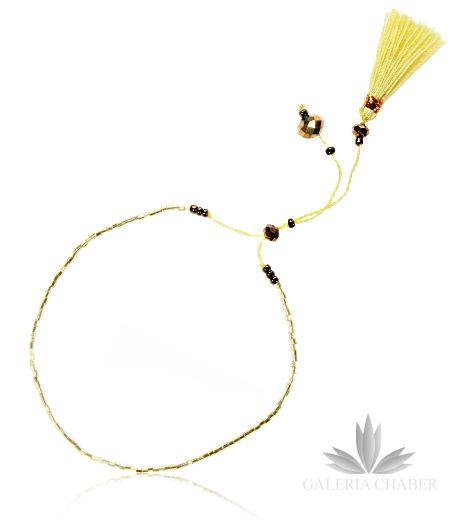 Bransoletka w stylu boho wykonana z mocnego, delikatnego sznurka i kryształków oraz koralików w kolorze złotym. Dodatkowo możliwość regulacji długości. Sznureczek dodatkowo ozdobiony frędzelkami z miękkiej bawełny.