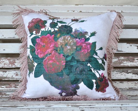This double sided cushion has pink and red roses on a white background surrounded by blue/green foliage on the front, and denim on the back.