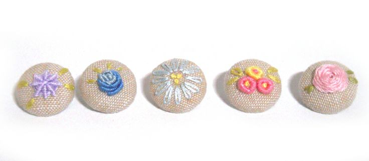 These are 5 different fabric covered buttons with flower embroidery.