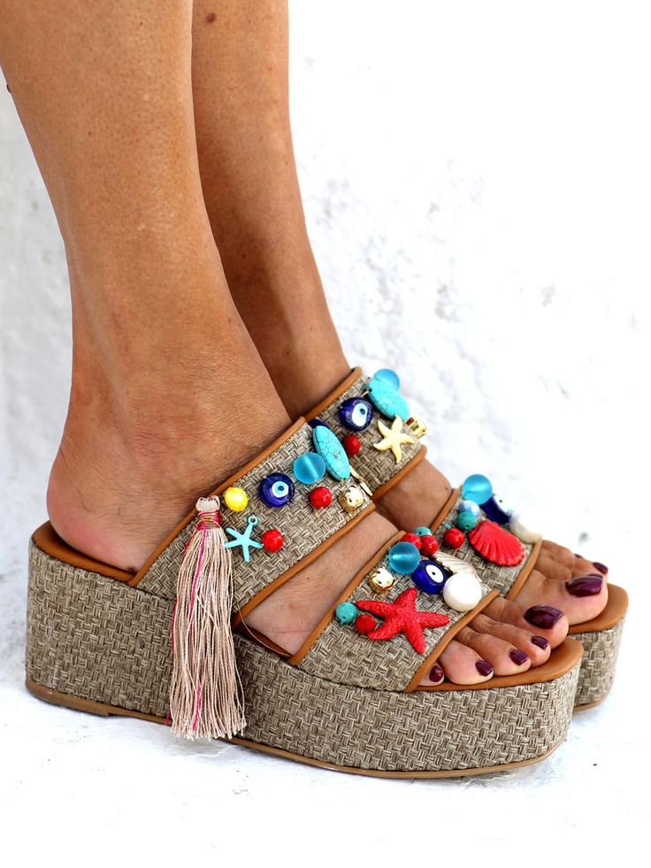 These flatform sandals are inspired by the duality of St. Tropez, a serene village that during the summertime is transformed in a jet-set destination. Same do these sandals combine simplicity with elegance. Set on a raffia flatform wedge, the sandals are adorned by hand with wonderful beading like evil eyes, pearls and starfish studs. They can be easily worn from morning till night, preferably combined with a simple dress or your favorite jeans.