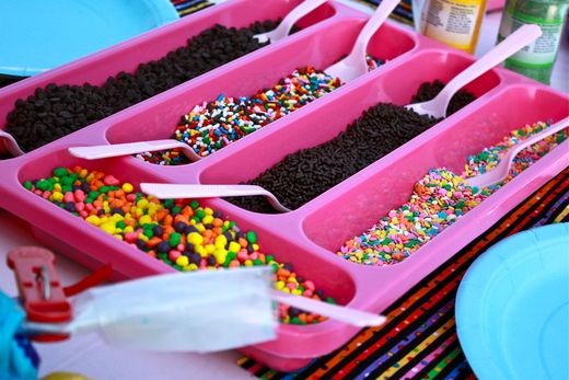 Display ice cream toppings in fun colored utensil trays.