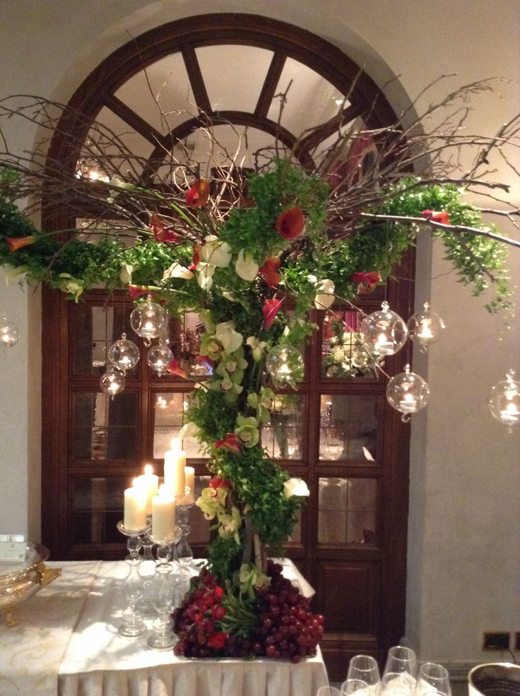 Tree made of greenery, branches and flowers with hanging boules with candles