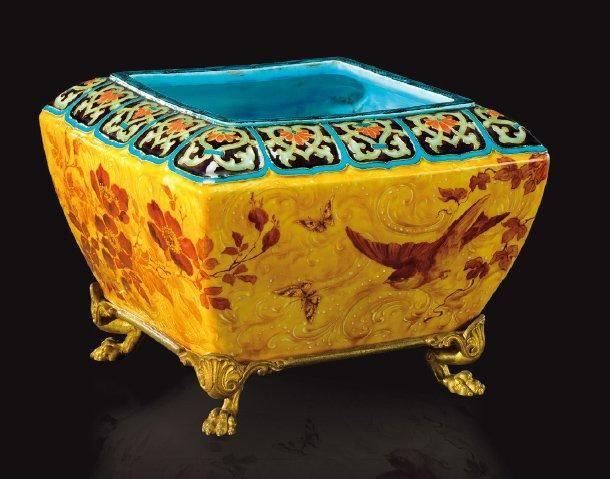 THEODORE DECK (1823-1891) Jardinière quadrangulaire à panse bombée en céramique émaillée à décor polychrome floral rehaussé de feuilles d'or sur fond jaune ocré. Elle repose sur une base en bronze doré - Aguttes - 08/10/2014