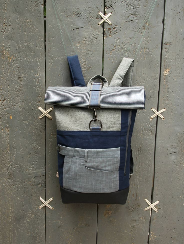 The front pocket from an azure striped men's suit trousers has been used on the front creating a double pocket in this upcycled roll top rucksack, by 'eating the goober'