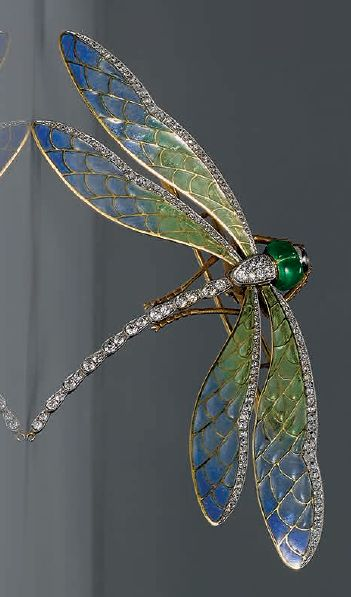 Enamel and diamond 'Dragonfly' brooch, circa 1900. Modelled as a dragonfly, the wings composed of plique-à-jour enamel in shades of blue and green, trimmed by rose-cut diamonds, the body designed as a line of circular-cut diamonds, to a green enamel head, the diamonds together weighing approximately 2.40 carats, mounted in 10 karat white and yellow gold. #ArtNouveau #brooch