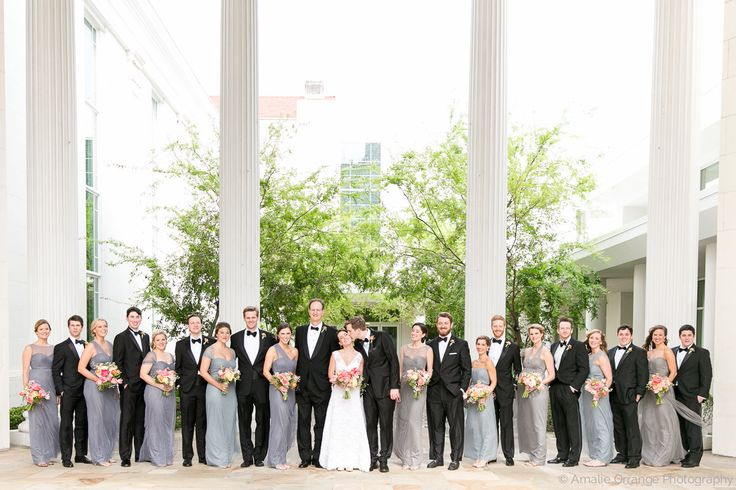 a stunning wedding party of groomsmen in classic black tuxedos and bridesmaids wearing gowns in shades of pale blue, pale grey and slate carrying loose spring bouquets of pink, blush, peach, ivory and greenery.