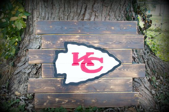Rustic burned wood Kansas city Chiefs Football sign. Each sign is hand torched to achieve a rustic barn wood look and feel. Each sign is hand made and wood grains may differ from picture to picture as each piece is unique. You may choose to have it painted or be left natural. This is the perfect edition to any man cave, den or even your favorite spot to watch the game! Gift for the KC Football fan, KC Chiefs house warming gift, Chiefs Christmas gift  21 tall by 27 long and is hand crafted…