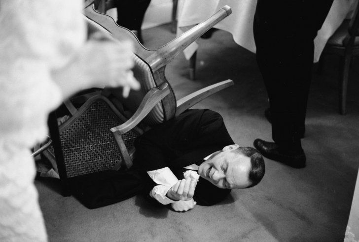 Frank Sinatra falls off his chair howling at a joke told by Joe E. Lewis, Miami 1965. Photo by John Dominis.