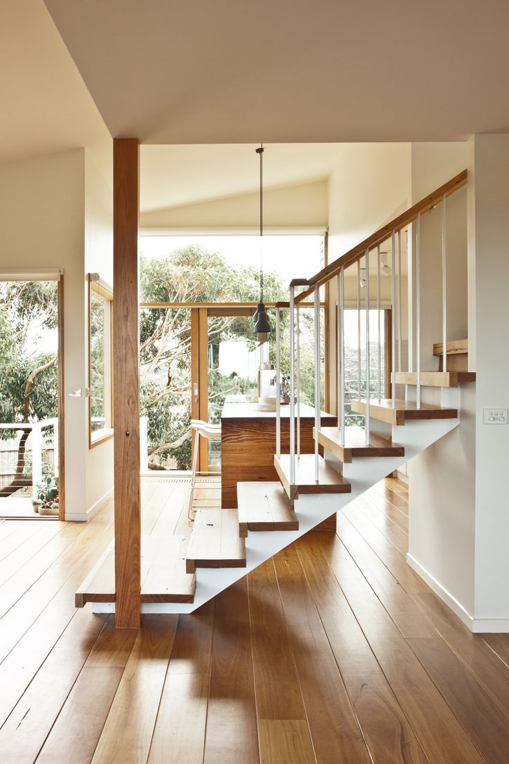 Light wood staircase in airy foyer of window filled house