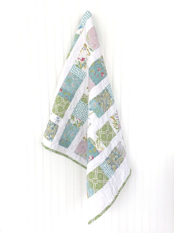 Our modern patchwork quilts make a wonderful gift for expecting moms or new babies! Measuring approximately 36 x 45, this quilt is a generous size to drape over a crib and transitions to toddler bedding. Use as a play mat on the floor, for cuddling and snuggling, or roll it up and take it to the park or beach!  Product Construction  This baby quilt was made with the highest quality designer cotton. It features shades of pastel pink, blue, green, and white. Constructed of three layers: a…