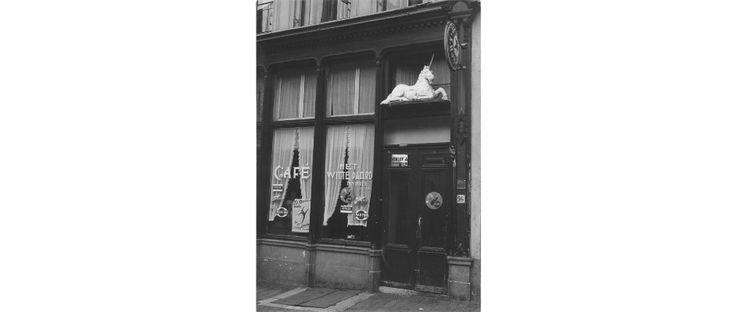 """Café """"Het Witte Paard"""" aan de Grotestraat 96 (vroeger """"De Eenhoorn"""" geheten naar het wit geschilderd houten beeld van een liggende eenhoorn boven de cafédeur). Op de ruit naast de deur staat de naam van de eigenaar Jan Duits."""