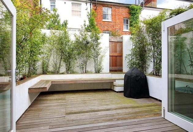 Tunbridge Wells, Kent. Nice solution for a small garden/patio. I like the raised beds, white rendered walls and benches.