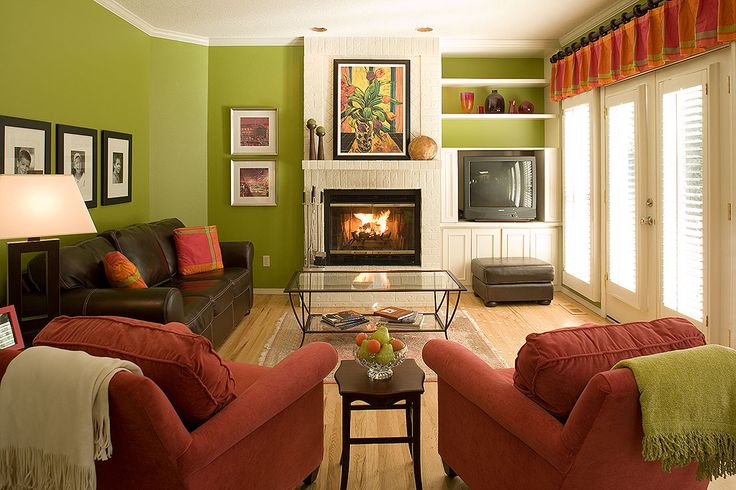 Great placement with family photos over the sofa small pair to the left of the fireplace and dramatic painting over the mantel pulling in all the colors of the room.