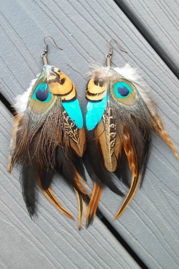 Dance all night in these exotic feather earrings with peacock eyes peeking at sparkling blue feathers in browns. by Diesel Boutique