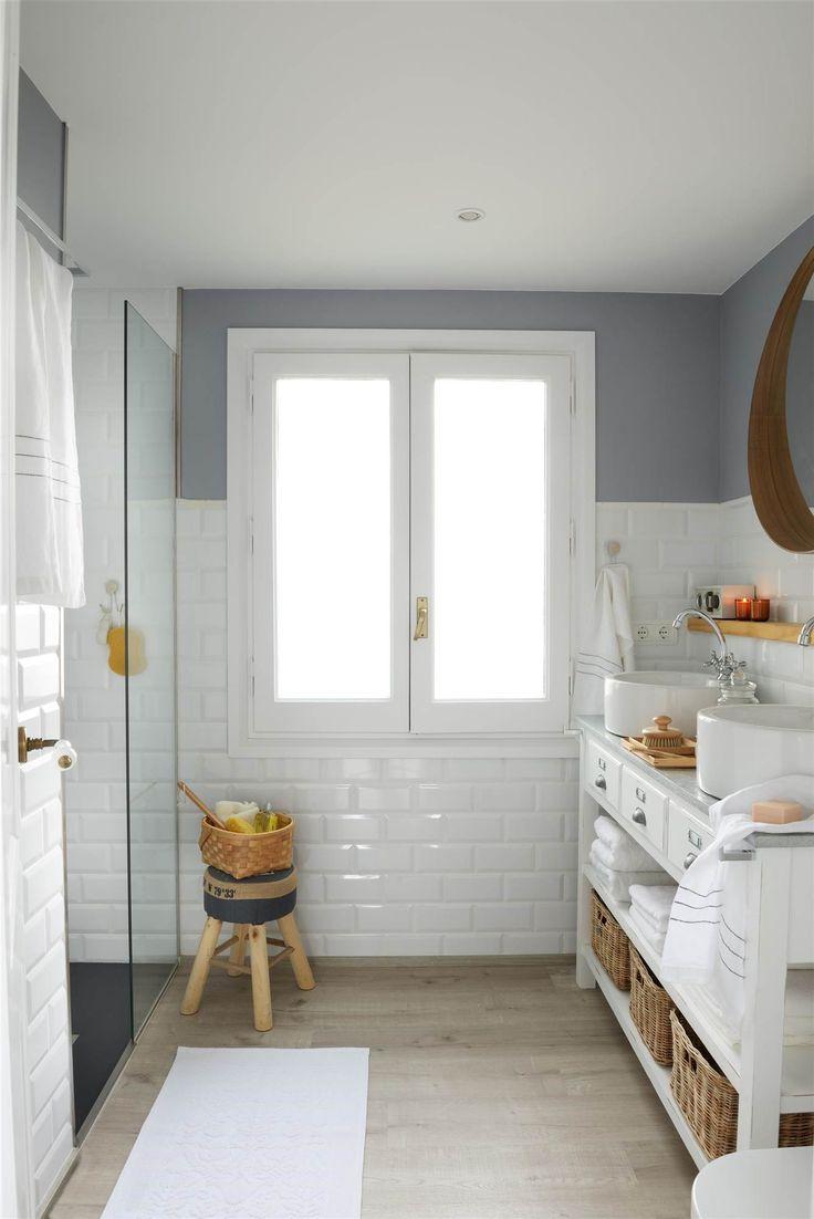 Dale color Si ya has colocado una tarima actual y los azulejos son blancos, puedes arriesgar pintando ese trozo de pared de un color gris oscuro. El mueble bajo lavabo es de Maisons du Monde, el lavamanos modelo Terra es de Roca y el pavimento de madera modelo Harmony es de Floover Flooring.