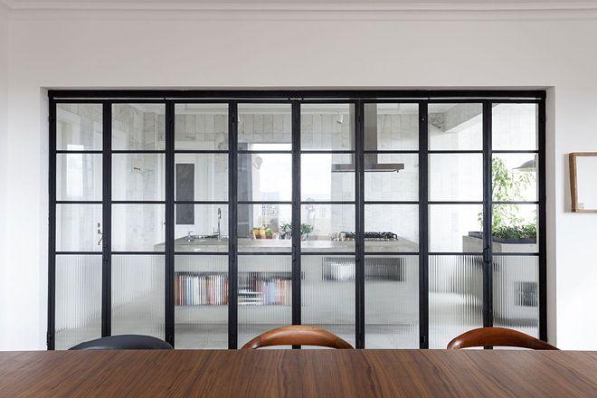 Перегородка из стекла и металла между кухней и столовой очень соответствует атмосфере квартиры.