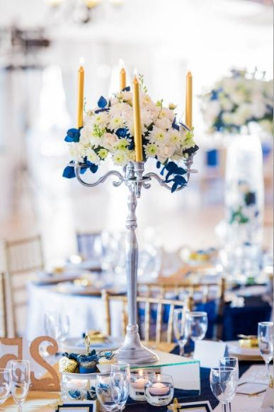 Monte Vista Venue navy blue and gold centerpiece with a medium arrangement that has navy blue sprayed leaves and gold butterflies in the center of the candelabra with gold candles on, all on a mirror box surrounded by 4 floating candles in glass bowls.
