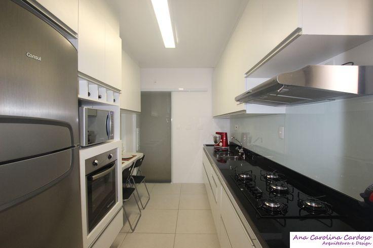Armários brancos e revestimentos claros proporcionam maior amplitude a cozinha.  Bancada em granito preto e revestimento em vidro no frontão da bancada, fecham a composição.