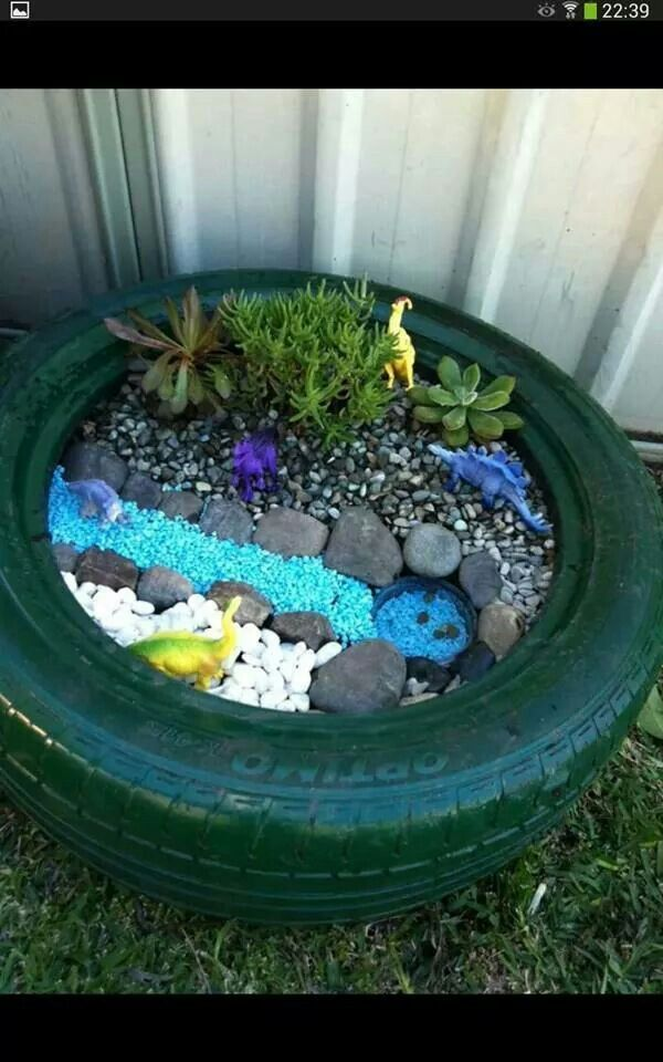 old tire turned dinosaur small world thinking one of these for my son to do and a fairysucculent garden for me