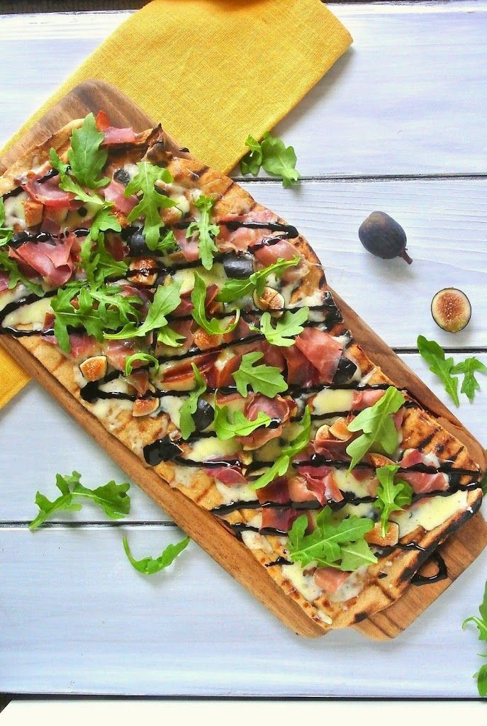 Whole wheat grilled flatbread with figs, prosciutto, arugula with a sweet balsamic glaze and fontina cheese. It's a healthy pizza.
